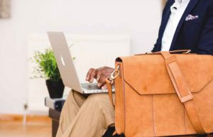 Man uses a laptop, leather satchel bag in front of him